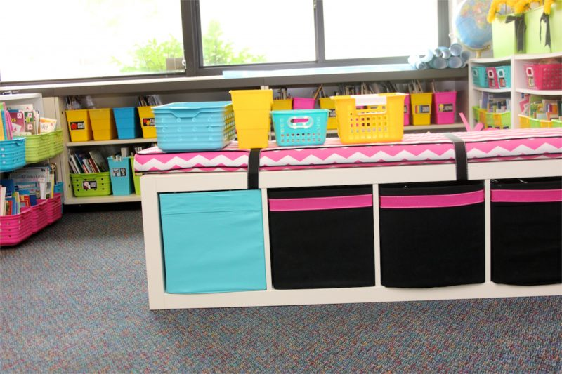 classroom library with teal and yellow bins