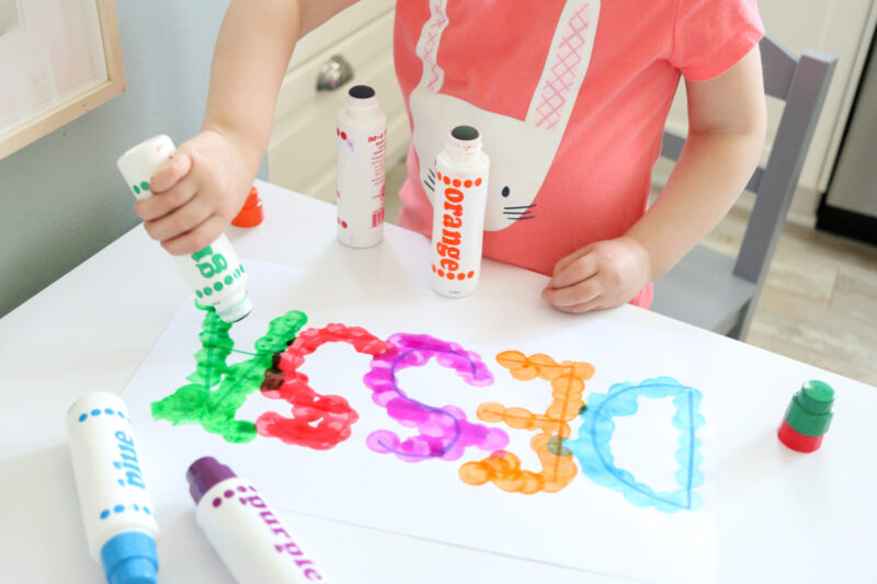 child using green, blue, orange, red and purple dot markers to trace letters in name