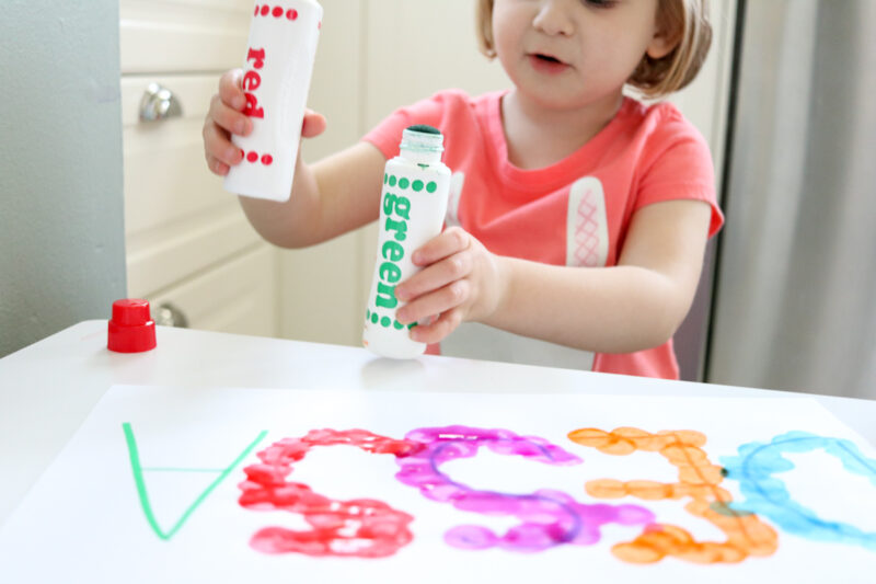 toddler playing with do-a-dot markers while tracing name
