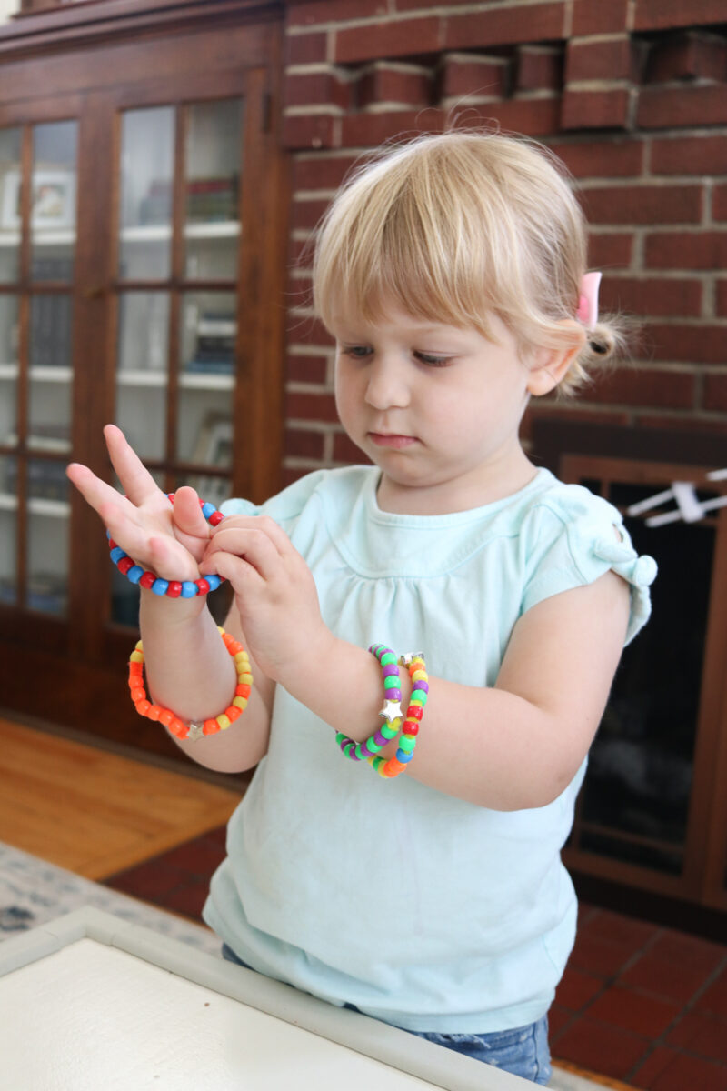 Looking for easy toddler activities? Use pony beads and pipe cleaners to create a simple bracelet. It's a great way to develop fine motor skills and work on pincer grasp. Make the activity even more meaningful by encouraging your child to make patterns. Pattern bracelets are a great mess-free activity for 3 year old and 4 year old children to work on at-home or in a preschool classroom.