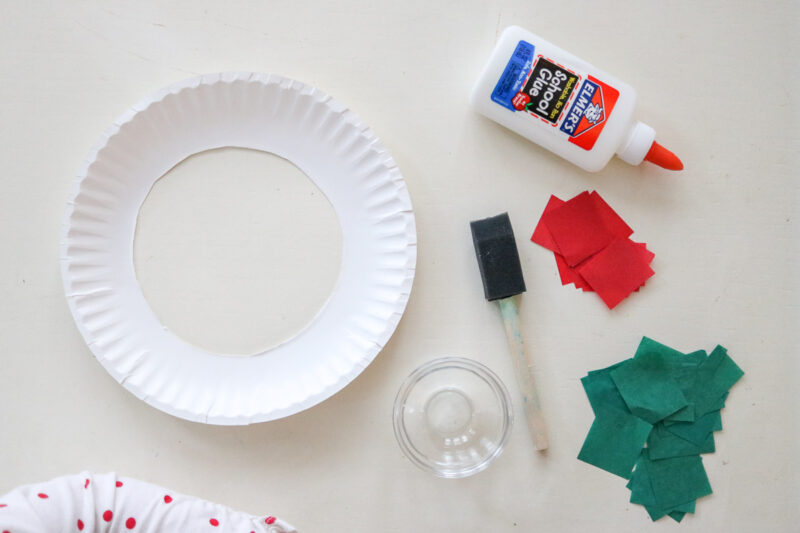 Paper Plate Christmas Wreath craft supplies: tissue paper, glue, paper plate and foam paintbrush