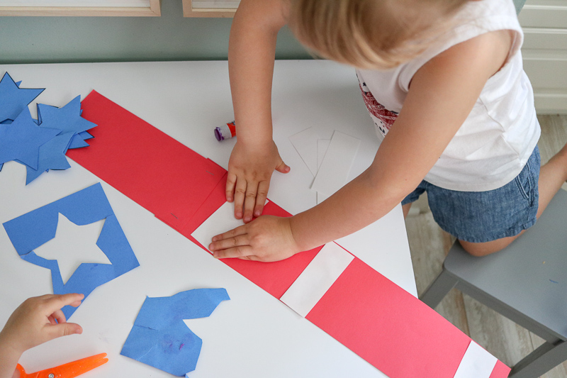 gluing red white and glue 4th of July hat craft for kids