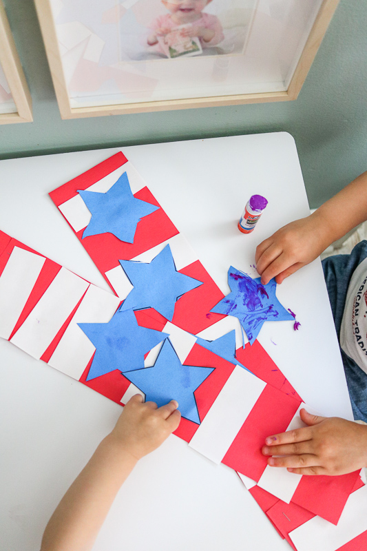 glueing blue construction paper stars onto 4th of July patriotic kids hat craft